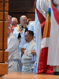 Toua Vang waits for hands laid upon him at his ordination June 27 in Breck School Chapel, Golden Valley.